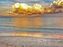 在海滩的金黄云彩 免版税库存图片