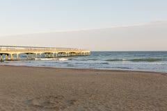 在海滩的金黄日落光在一个码头在欧洲 图库摄影