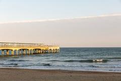 在海滩的金黄日落光在一个码头在欧洲 免版税图库摄影