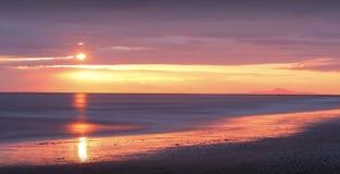 在海滩的金黄日落 免版税库存照片