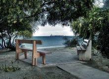 在海滩的长凳 免版税库存照片