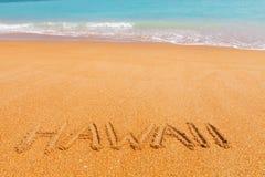 在海滩的题字夏威夷由蓝色海 图库摄影
