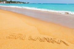 在海滩的题字斯里兰卡由蓝色海 库存照片