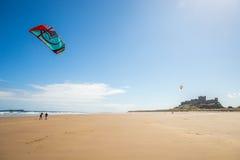 在海滩的风筝在Bamburgh城堡 库存图片