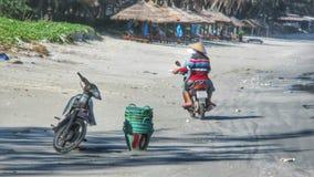 在海滩的骑马摩托车 免版税库存图片