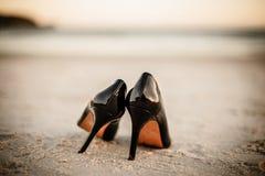 在海滩的黑专利鞋子 库存照片