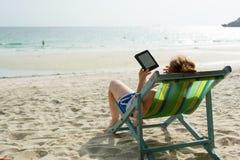在海滩的读书e书 免版税库存照片