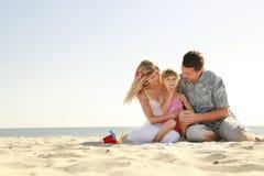 在海滩的年轻家庭 免版税库存图片