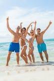 在海滩的年轻愉快的朋友havin乐趣 免版税库存图片