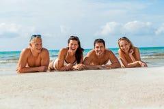 在海滩的年轻愉快的朋友havin乐趣 库存照片