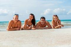 在海滩的年轻愉快的朋友havin乐趣 免版税图库摄影