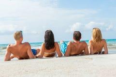 在海滩的年轻愉快的朋友havin乐趣 库存图片
