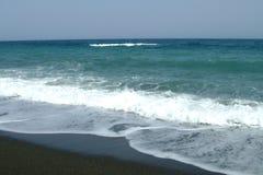 在海滨的黑沙子 免版税库存图片