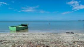 在海滩的绿色小船 图库摄影