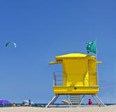在海滩的黄色救生员塔与人、风筝冲浪者和蓝天 免版税库存图片