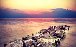 在海滩的紫色日落,平安的海风景 免版税库存照片