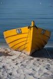 在海滩的黄色渔夫` s小船 免版税库存图片