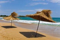 在海滩的细长的伞。 免版税库存照片