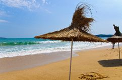 在海滩的细长的伞 免版税库存图片