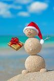 在海滩的兴高采烈的含沙雪人在有金黄礼物的圣诞节帽子 免版税库存图片