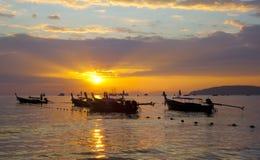 在海滨的Longtail小船在日落 库存照片