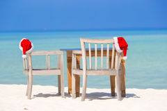 在海滩睡椅的红色圣诞老人帽子热带假期 免版税库存照片