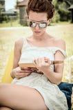在海滩礼服和太阳镜的美丽的女孩阅读书 库存图片