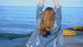 在海滨站立并且发展头发的俏丽的女孩游人,享受自然在晴天 股票录像