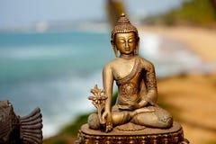 在海洋背景的菩萨黄铜雕塑 库存照片