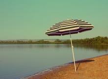 在海滩-葡萄酒减速火箭的样式的阳伞 免版税库存图片
