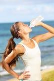 在海滩赛跑以后的健身妇女饮用水 免版税库存图片