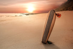 在海滩踩滑板在日落,青年和自由概念 图库摄影