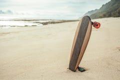 在海滩踩滑板在日落,青年和自由概念 库存图片