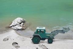 在海滩边附近的地球搬家工人 库存图片