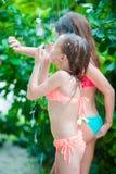 在海滩阵雨下的可爱的小女孩在热带海滩 库存图片