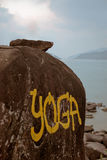 在海洋附近的大石头有黄色标题瑜伽的 库存照片