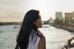 在海洋附近的美丽的亚裔夫人在日落期间 免版税库存照片