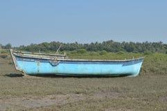 在海滨附近的蓝色小船 免版税库存照片