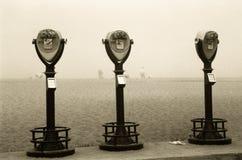 在海滩雾的减速火箭的双筒望远镜 免版税库存照片