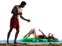 在海滩饮用的夫妇 免版税图库摄影
