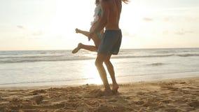 在海滩,人拥抱的年轻夫妇和转动他的日落的妇女 女孩跳进她的男朋友胳膊,他旋转 影视素材