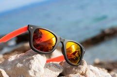 在海滩,假日概念的太阳镜 免版税图库摄影