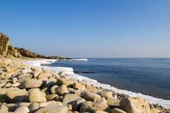 在海滩,冬天冰的海石头 库存图片