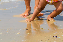在海滩,有孩子的一个母亲,家庭的儿童的和成人脚 免版税图库摄影