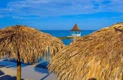 在海滩,蒙特哥贝牙买加的茅草屋顶伞 库存照片