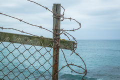 在海洋clifftop的铁丝网篱芭 图库摄影