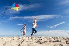 在海滩Flting的家庭风筝 免版税库存图片