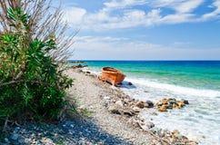 在海滩Platanaki的被放弃的橙色小船 免版税库存照片