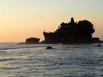 在海Tanah全部的一个岩石兴建的著名寺庙在日落用Bal,印度尼西亚 库存照片