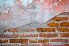 在涂灰泥的水泥前的未加工的砖墙 免版税库存图片